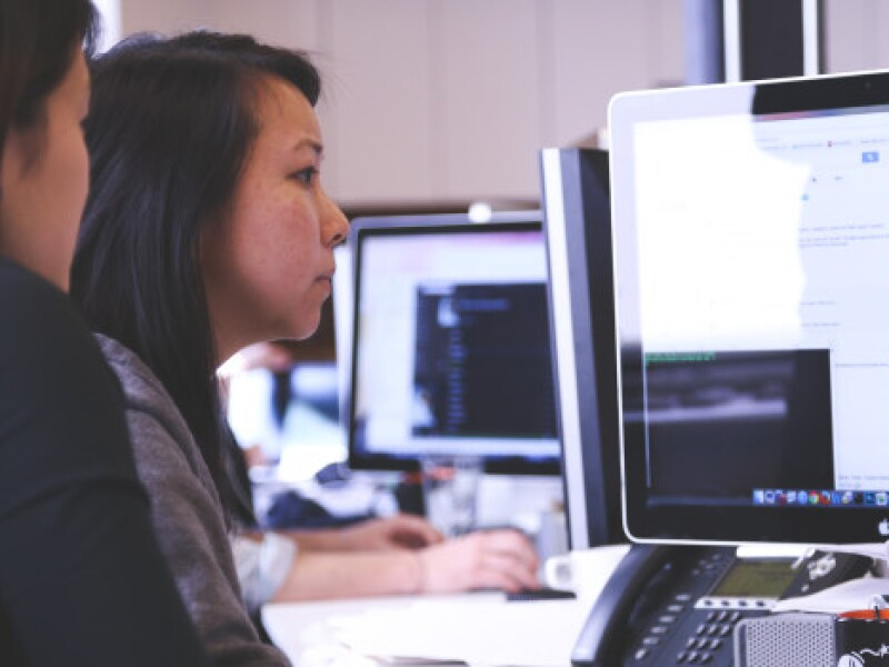 Two women sit at a desk and look at information displayed on a flat screen computer monitor. In this blog post, Lingjie Zhang—a Software Engineer at Perfect Sense/Brightspot—explains why she finds code review to be essential.