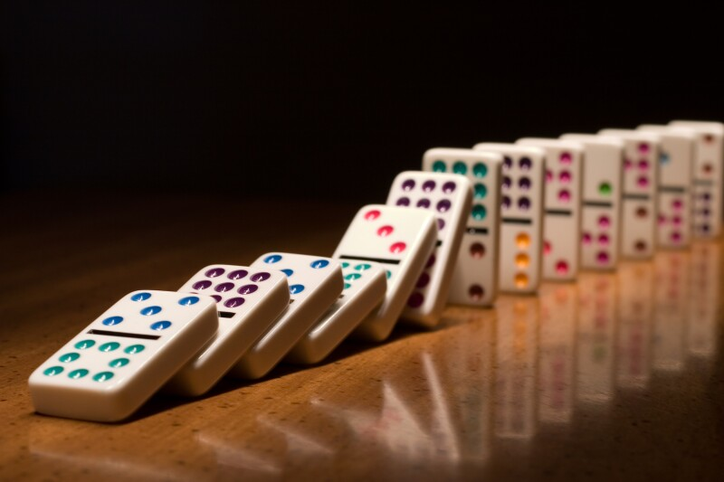 A lined up set of dominoes falling on top of one another