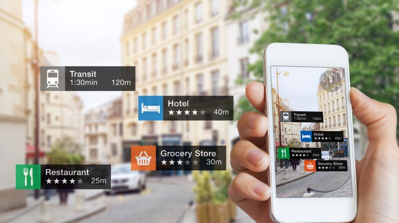 A graphic shows a hand holding a smartphone in a city setting. The phone is displaying transit options, ratings for hotels, grocery stores and restaurants.