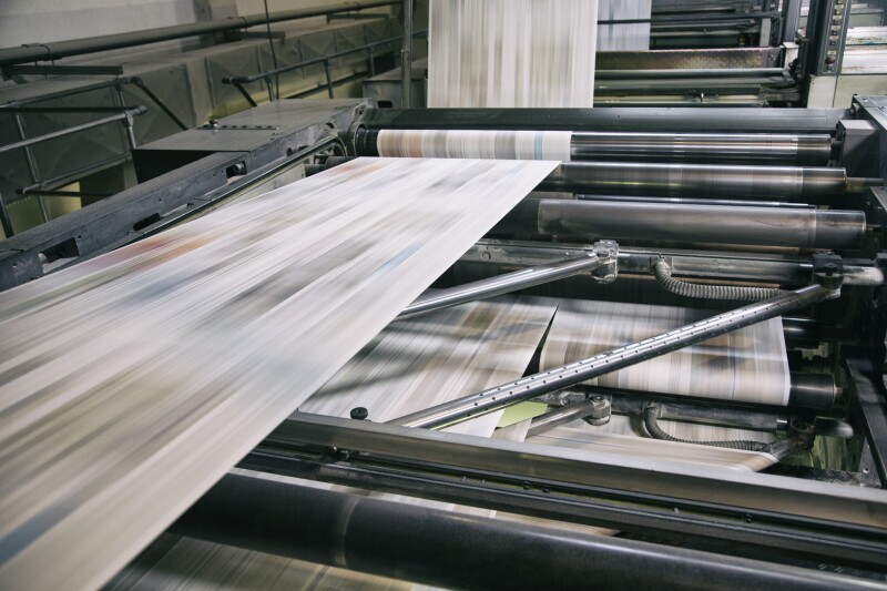 This picture shows a printing press for a newspaper in action with a blurry shot of newspapers in the printing process