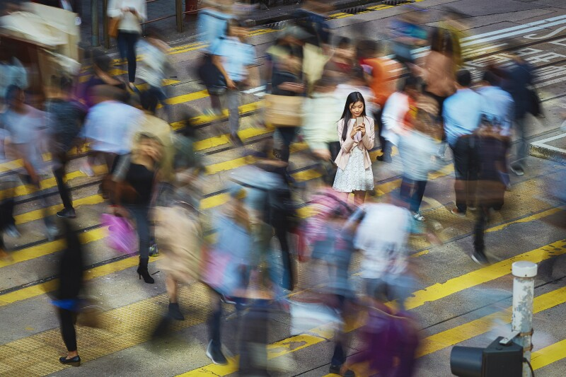Businesswoman using mobile phone amidst crowd
