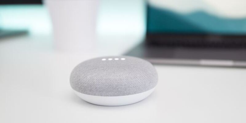 A small gray and white smart speaker sits on a clean white surface with an open laptop in the background. This blog post explored CMS Media Trends and CMS Trends from 2018.