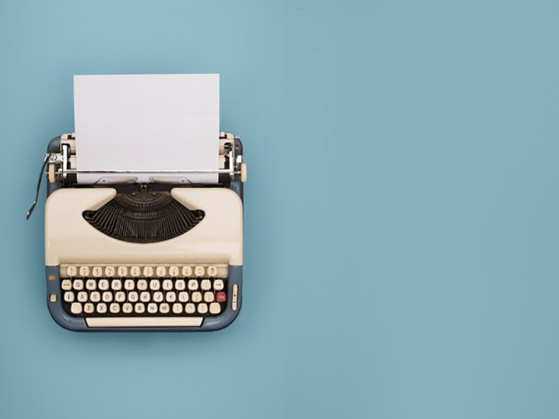 An old white typewriter is seen from above as it sits on a blue background to illustrate brand storytelling