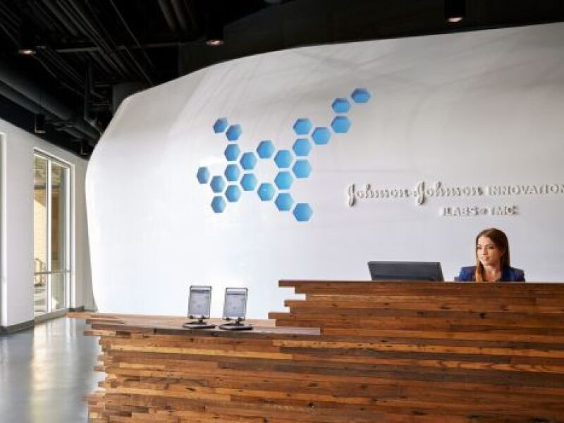 A receptionist sits behind a wooden desk in front of a Johnson and Johnson sign. Learn how Johnson & Johnson revamped its corporate communications strategy with its Global Content Lab.