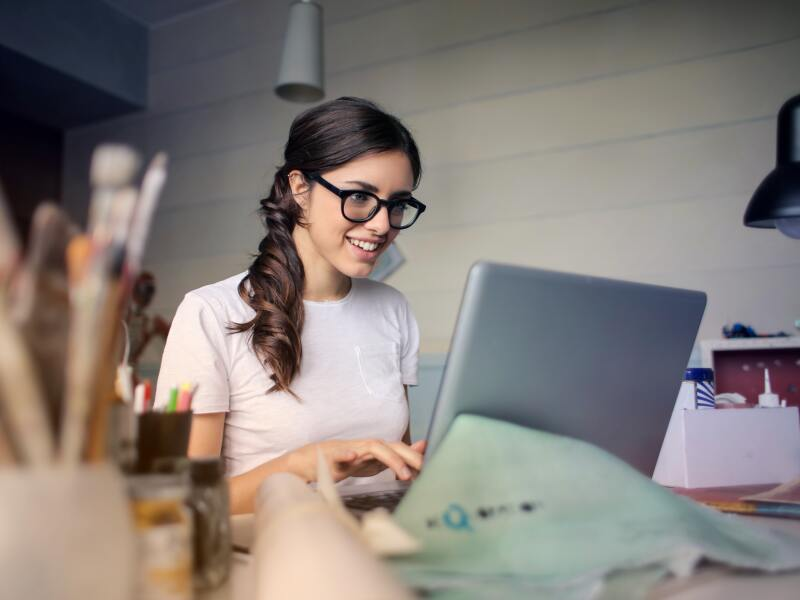 A young woman with glasses is sitting at a desk looking at a laptop with art supplies in the foreground