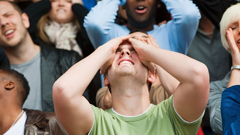 This image shows a closeup of a crowd of people expressing frustration by cringing and putting their hands on their heads in dismay.
